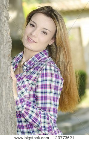 beautiful girl leaning against a tree looking at the camera