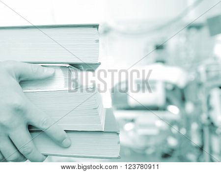 Stack of book in hands of young trainee doctor.