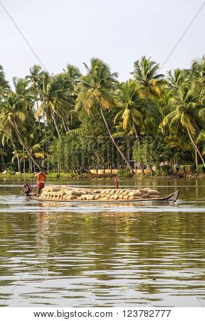 KERALA, INDIA - OCTOBER 16, 2015: Unindetified men at backwaters in Kerala India. The backwaters are an extensive network of 41 west flowing interlocking rivers lakes and canals that center around Alleppey Kumarakom and Punnamada.