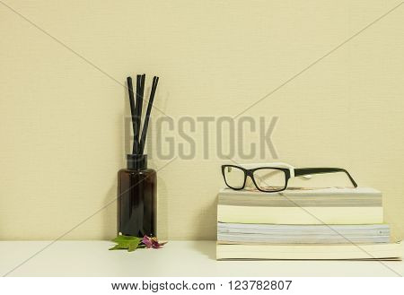 Glasses on books with bottle of perfume background