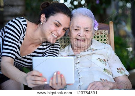 grandma and granddaughter taking a selfie with a tablet