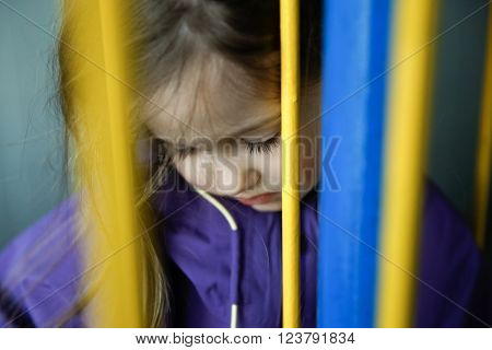 Thoughtful and sad little girl hiding behind fence, feeling blue and distressed. Childhood, growing up, neglection, disappointment, loneliness and sadness concept.