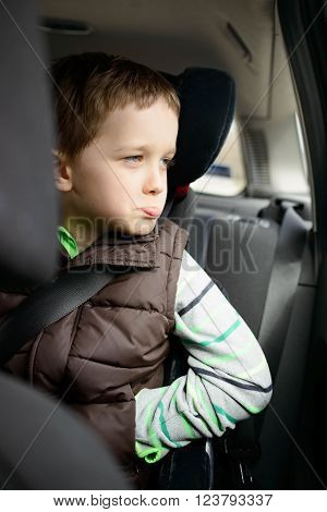 Offended little boy in car safety seat. Children car safety concept. Looking through the window