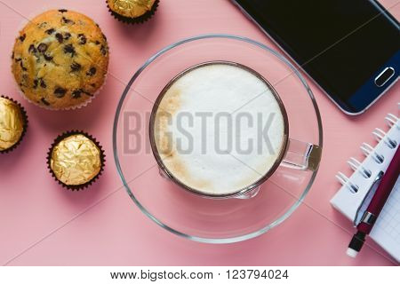 Cup of Cappuchino with dessert and a phone with blank screen and a notebook with pen on a pink background