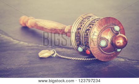 Vintage stylized old Tibetan prayer wheel used to accumulate wisdom and good karma and to purify bad karma, shallow depth of field.