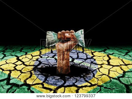 degraded hand holding money coming out of hole in painted cracked ground with the flag of Brazil