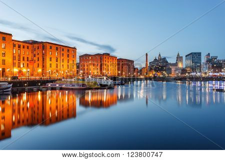 Reflections of old buildings at Albert Dock Liverpool waterfront UK.