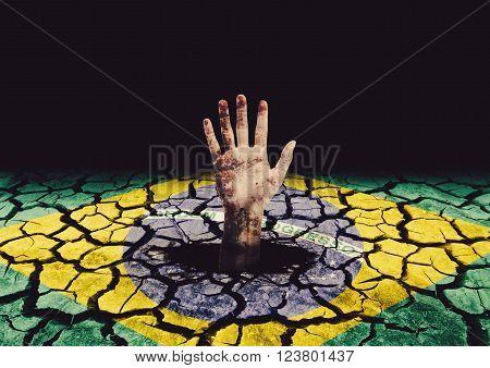 degraded hand coming out of hole in painted cracked ground with the flag of Brazil
