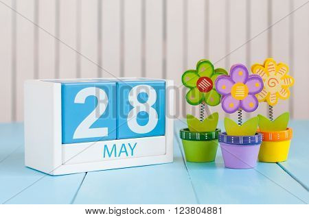 May 28th. Image of may 28 wooden color calendar on white background with flowers. Spring day, empty space for text.