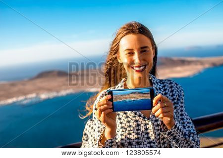 Woman showing smart phone screen with great view on Graciosa island standing on El Rio viewpoint on Lanzarote island in Spain