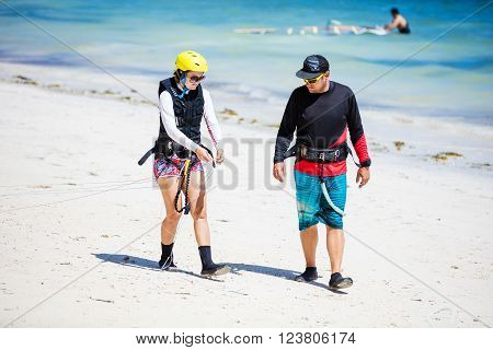 Kitesurfing instructor and female student preparing lines on beach