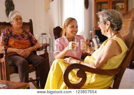 Old people in geriatric hospice: young attractive hispanic woman working as nurse helps a senior woman. She gives a water glass and prescription medicine to the aged patient poster