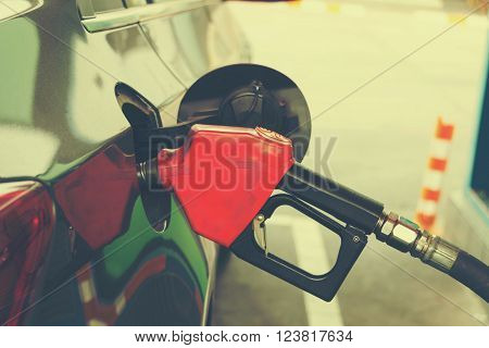 filling gasoline into car at gas station