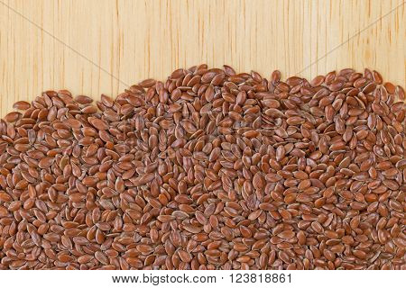 Reddish Brown seeds of Linseed, also called flaxseed on wooden background with copyspace. Flaxseed are seeds from flax plant