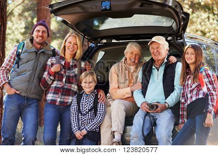 Multi generation family standing by a car before forest hike