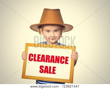 Little Funny girl in striped shirt with blackboard. Text  clearance sale.  Isolated on gray background