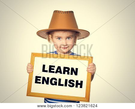 Little Funny girl in striped shirt with blackboard. Text  learn english.  Isolated on gray background
