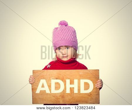 Little girl holding Board with inscription ADHD. Isolated on gray background