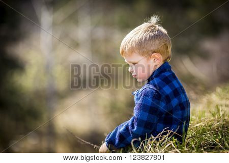 Sad little boy in plaid jacket sitting on the grass