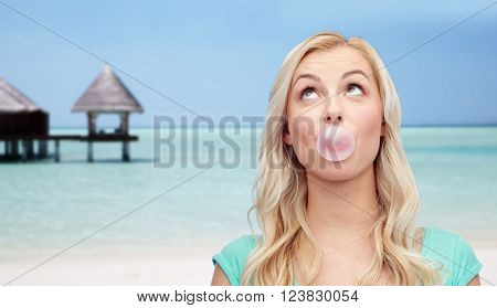 summer vacation, travel, tourism and people concept - happy young woman or teenage girl chewing gum over beach on touristic resort background