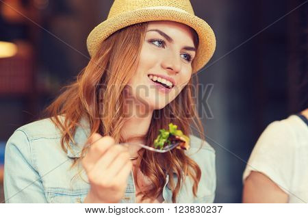 people, leisure, food and communication concept - group of happy smiling young woman with fork eating salad and meeting friends at bar or pub