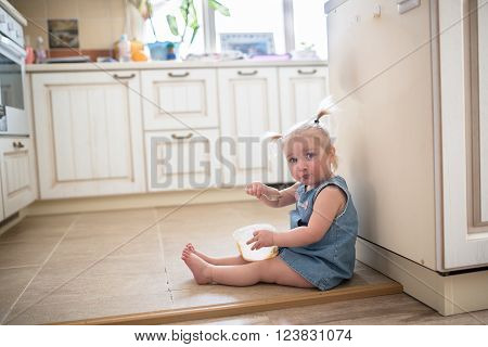 Little Caucasian Toddler funny girl with pigtails eating ice cream from a jar sitting on the floor in the kitchen casual lifestyle photo series in real life interior