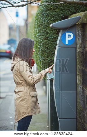 Woman using parking machine one the side of the street