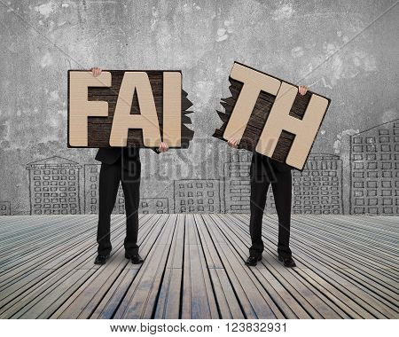 Men holding two cracked FAITH word wooden boards on wood floor with concrete wall background.