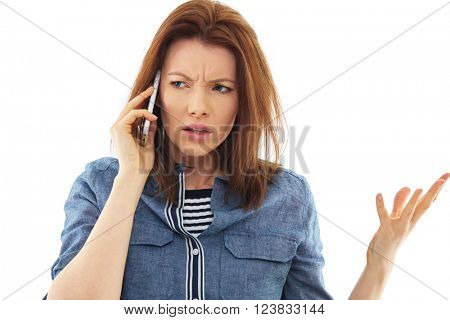 Stressed woman talks over her mobile phone, isolated over white background