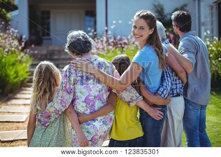 Cheerful woman with family standing in back yard