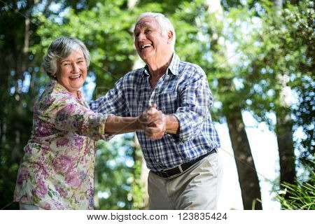 Happy senior woman dancing with husband against trees in back yard