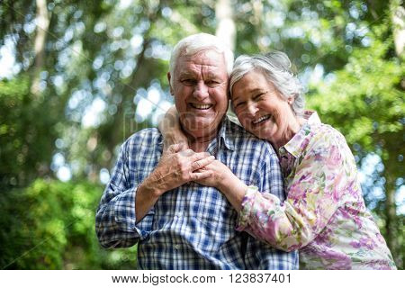 Happy senior woman embracing from behind husband against trees in back yard poster