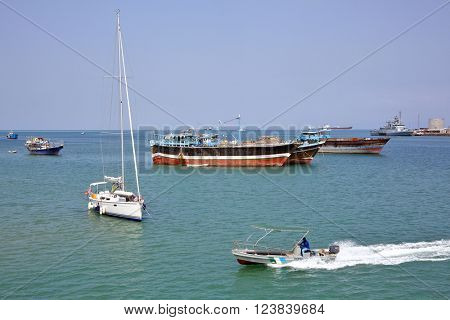 GULF OF ADEN, DJIBOUTI - FEBRUARY 08, 2016: Coast Guard boat goes by luxury sailing boat, fishing and cargo ships at anchor in the port of Djibouti