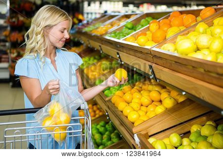 Smiling woman putting oranges in plastic bag at grocery shop