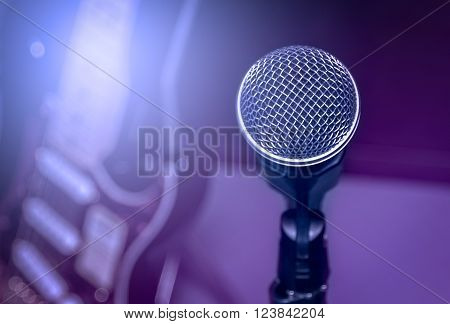 selective focus microphone and blur electric guitar background and flare light.