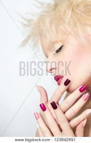 Burgundy multi-colored manicure and makeup on the blonde girl with the flower on his head.