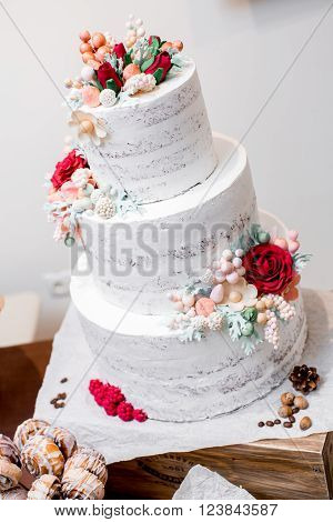 The delicious white wedding cake decorated flowers