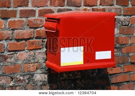 red post box on the old wall