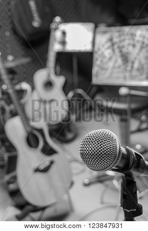 selective focus microphone and blur musical equipment guitar bass drum piano percussionist lyric background.