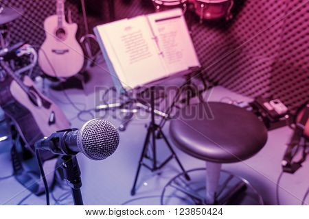 selective focus microphone and blur musical equipment guitar lyric drum piano background.