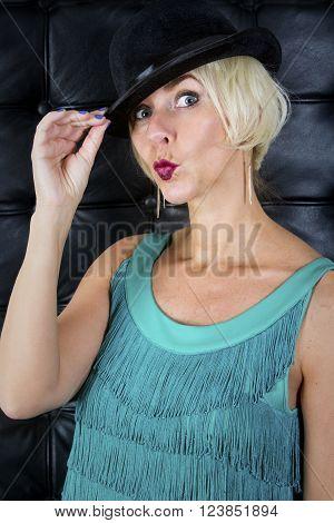 blond showgirl in green dress wearing a black hat