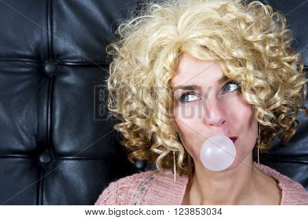 portarit of curly blond woman with bubblegum