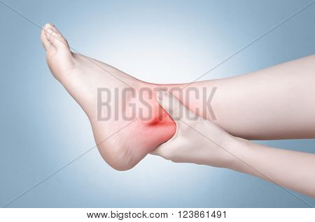 A young woman massaging her painful ankle