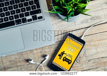 Taxi booking app on a mobile phone on a office desk.