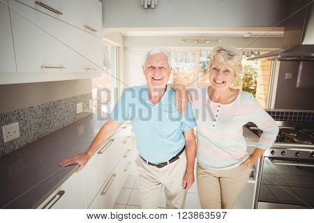Portrait of happy senior couple standing in kitchen at home