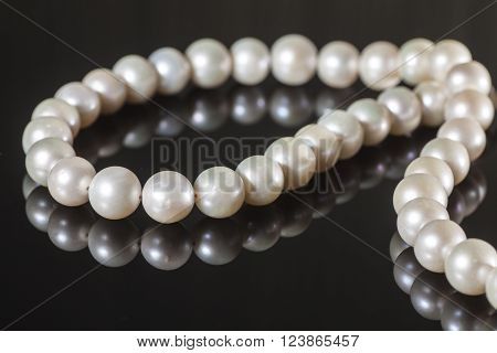 pearl necklace on a black background with reflection
