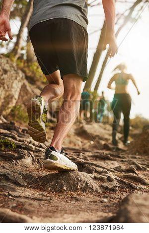 Closeup shot of a male runner on rough terrain outdoors. Trail running workout on hillside.