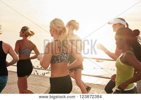 Shot of group of fit young women running together on road by the sea at sunset. Multi ethnic group of women doing running training outdoors.