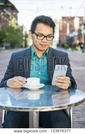 Successful young asian man in business casual attire sitting in outdoor cafe holding cup of coffee while using mobile device