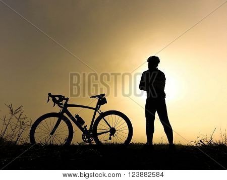 Bicycle rider stand on the hill watching the sunlight and relax